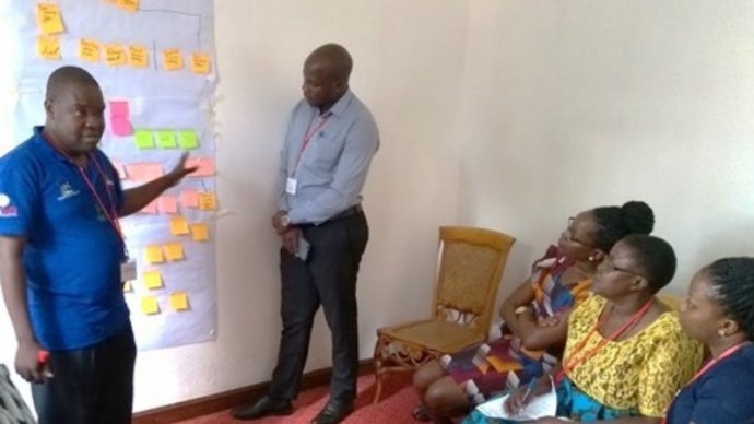Two members of the Wakiso team present their problem tree to reviewers from Luwero