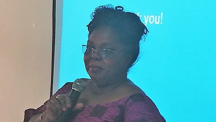 An African lady wearing a pink top and glasses speaks into a microphone