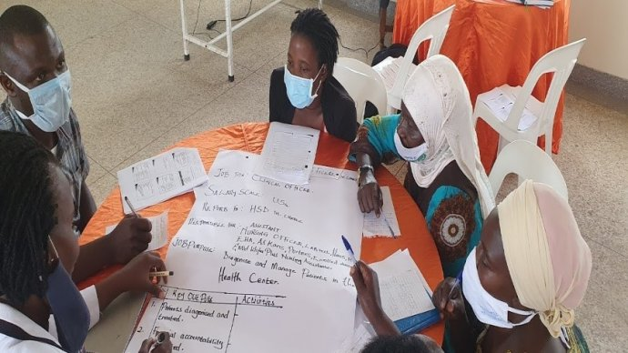 A group of masked African men and women discussing and writing on a piece of flipchart paper