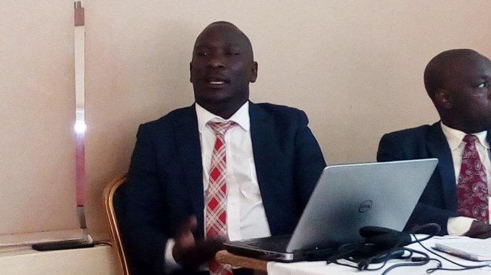 Seated African man in a suit speaking. He has a laptop open in front of him.