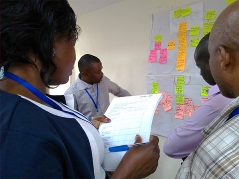 Members of the Nakaseke team us a checklist to review the strategies developed by the Wakiso team