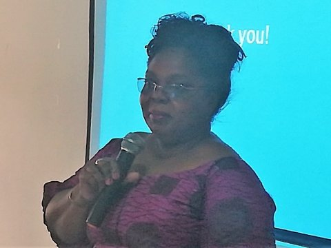 An African lady with a pink top and glasses speaks into a microphone