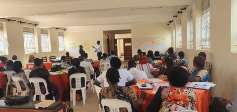 A group of about 30 African men and women, seated on white chairs while watchign man at the fron tof the room talking about a poster covered in post-its