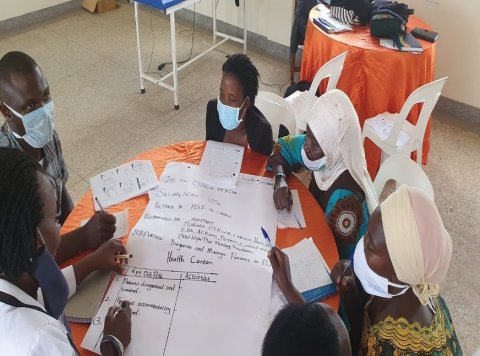 A group of masked African men and women sit around a table, writing on a piece of flipchart paper